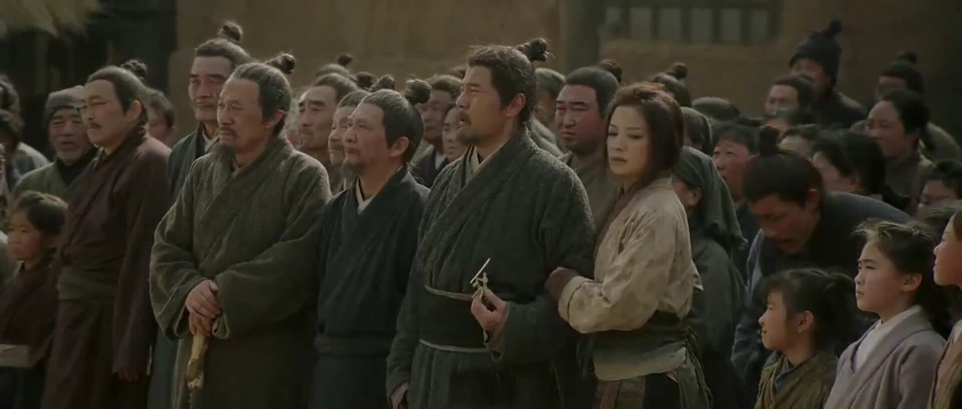 Mulan stands next to her father, Hua Hu, as he receives his conscription orders.